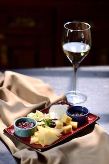 Tabla de quesos con salsa en un plato azul, copa de vino