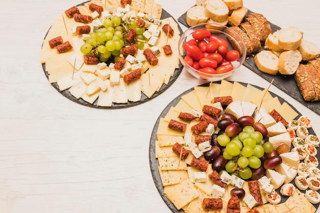 Tabla de quesos servida con tomates, rebanadas de pan y salchichas ahumadas en mesa de madera