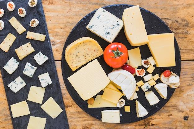 Tabla de quesos con tomates y mini sándwich en pizarra negra sobre la mesa de madera