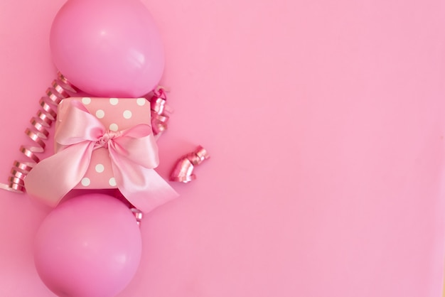Tabla del rosa en colores pastel con los globos y el confeti coloridos para la opinión superior del cumpleaños. estilo plano laico.