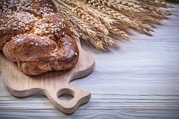 Tabla de talla trigo centeno orejas pan largo sobre fondo de madera comida y bebida concepto