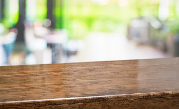 Tabla vacía de la madera dura de la perspectiva con la cocina de la falta de definición en bokeh del fondo del jardín