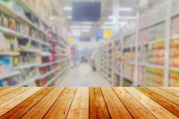 Tabla vacía del tablero de madera delante del fondo borroso. perspectiva de madera clara sobre el desenfoque en el supermercado: se puede usar para exhibir o montar sus productos. simulacro para mostrar el producto.