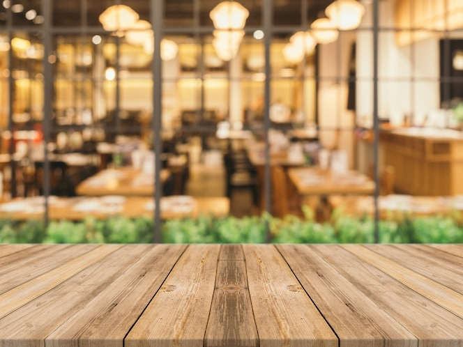 Tablas de madera con restaurante borroso de fondo
