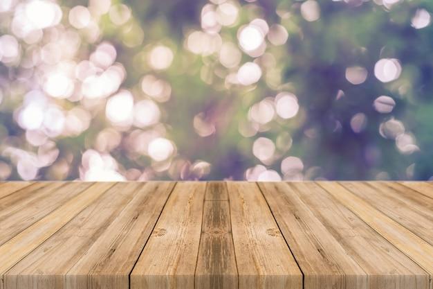 Tablas de madera con árboles desenfocados de fondo
