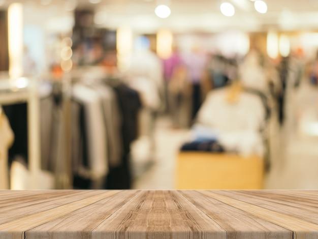 Tablas de madera con tienda de ropa borrosa de fondo