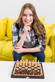 Tablero de ajedrez de madera en mesa blanca frente a mujer joven sonriente sentada en sofá
