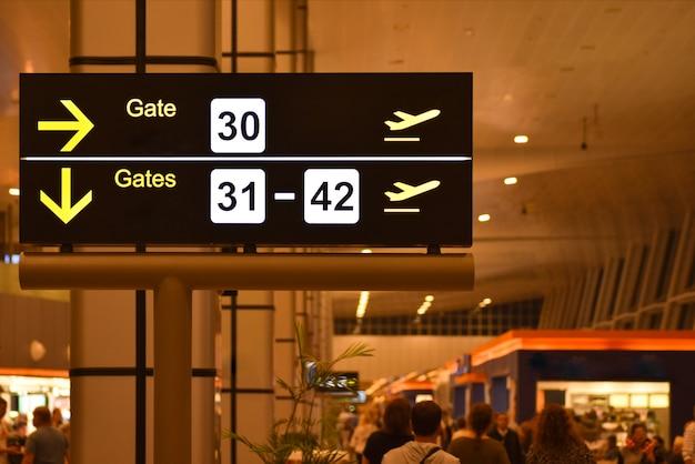 Tablero de anuncios digital con señales de puerta de enlace del aeropuerto.