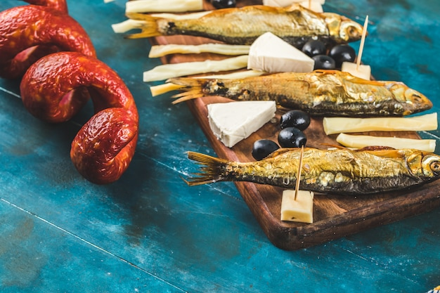 Tablero de aperitivos con rodajas de salchicha, cubitos de queso y aceitunas negras con galletas y pescado seco en la mesa azul