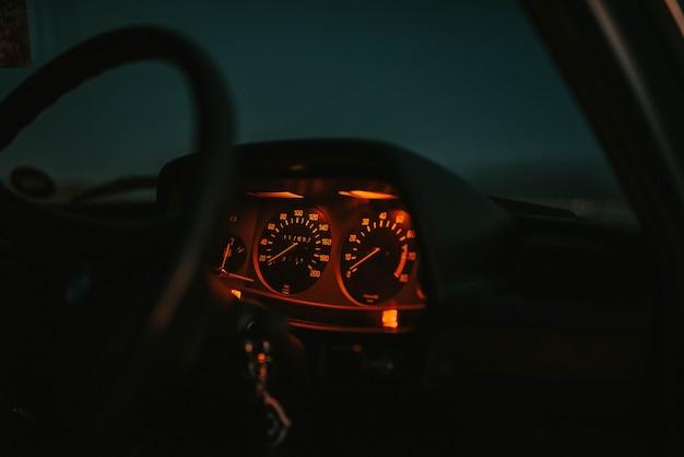 Tablero del automóvil iluminado en rojo con un volante por la noche