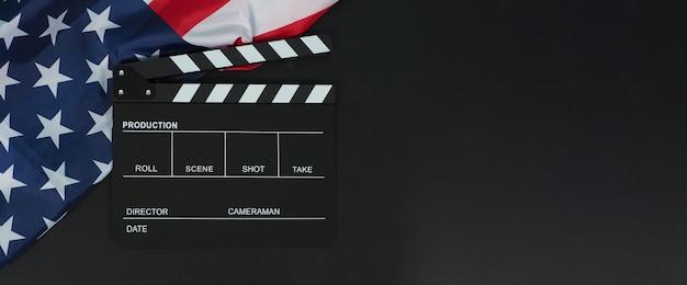 Tablero de azote negro o pizarra de película y bandera de los estados unidos de américa (ee. uu.) sobre fondo negro.
