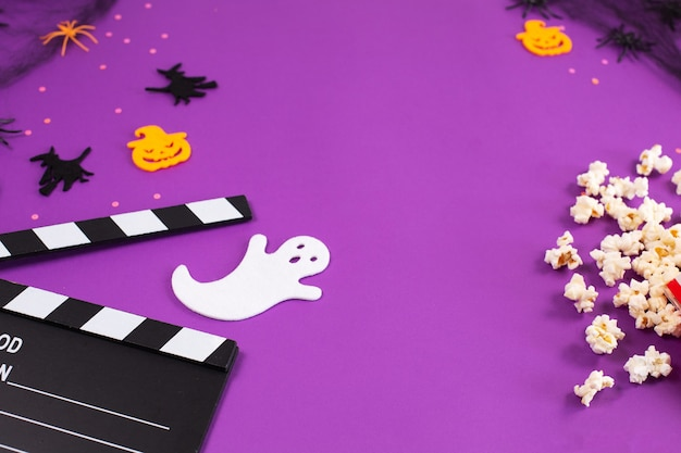 Tablero de azote de película en telarañas arañas ojos fantasma sobre fondo lila púrpura