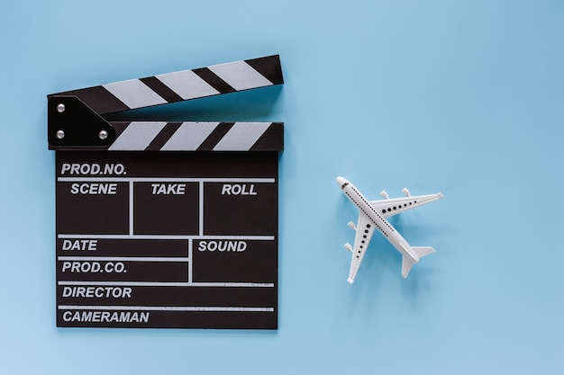 Tablero de badajo de película con modelo de avión blanco sobre fondo azul.