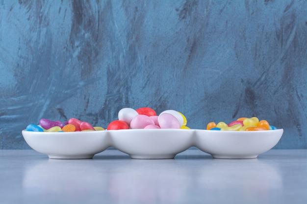 Un tablero blanco lleno de caramelos de frijoles coloridos sobre fondo gris. foto de alta calidad