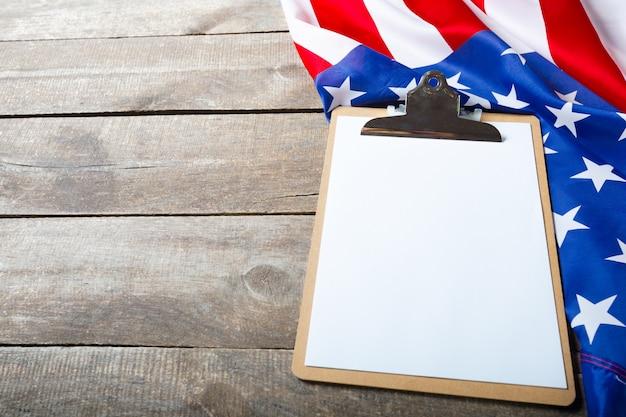 Tablero de clip en blanco y bandera de estados unidos sobre fondo de madera