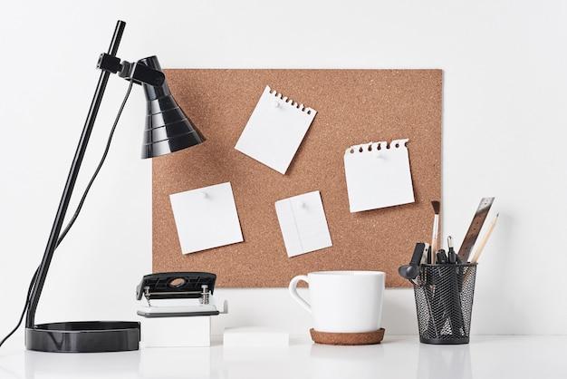 Tablero de corcho con material de oficina sobre fondo blanco.