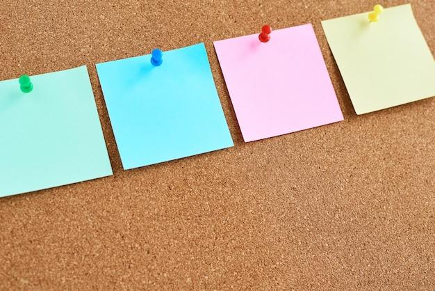Tablero de corcho con notas en blanco de colores clavadas
