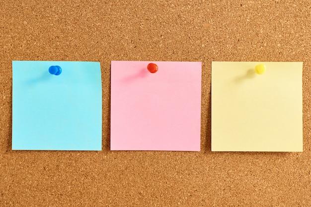 Tablero de corcho con notas en blanco de colores fijados