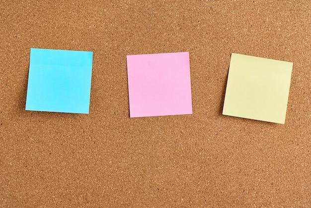Tablero de corcho con notas en blanco de papel de colores