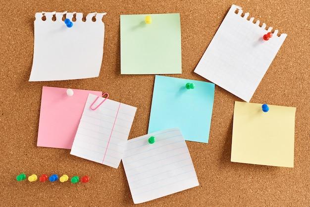 Tablero de corcho con un pinned notas en blanco de colores
