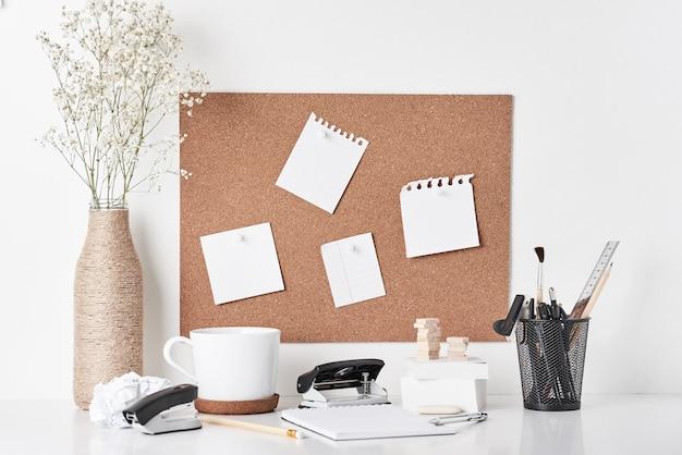 Tablero de corcho con suministros de oficina sobre fondo blanco