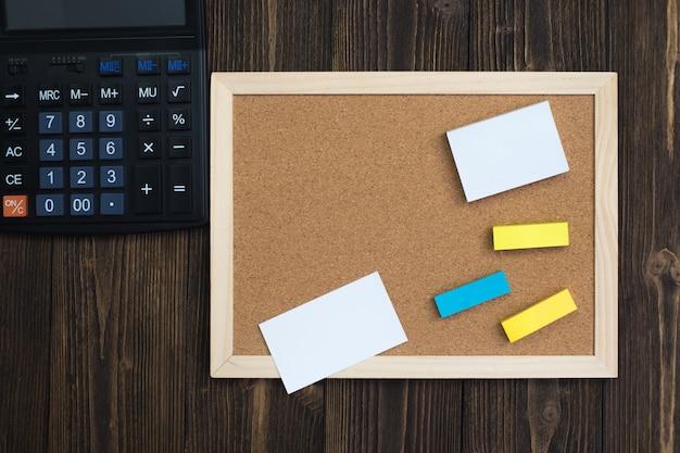 Tablero de corcho vacío con marco de madera y calculadora bloc de notas adhesivo sobre madera