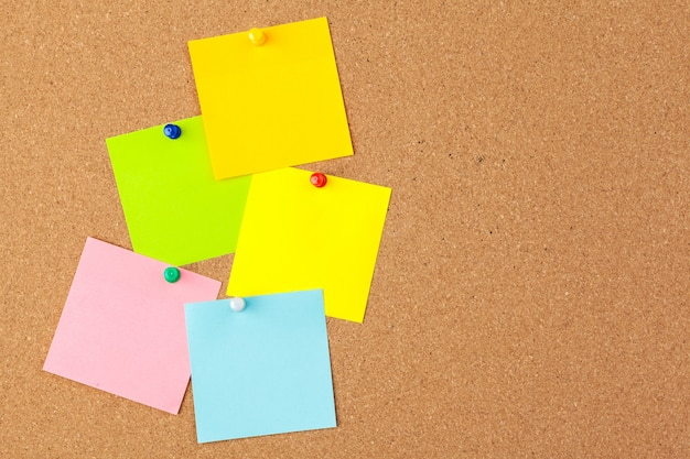 Tablero de corcho con varias notas en blanco coloridas con alfileres