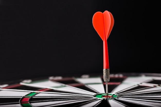 Tablero de dardos con flecha de dardo rojo en el centro del tablero de dardos. orientación, negocio y concepto de éxito.
