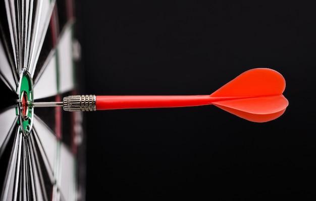 Tablero de dardos con flecha de dardo rojo en el centro del tablero de dardos.
