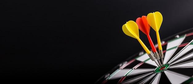 Tablero de dardos con flechas de dardos rojos y amarillos en el centro del tablero de dardos