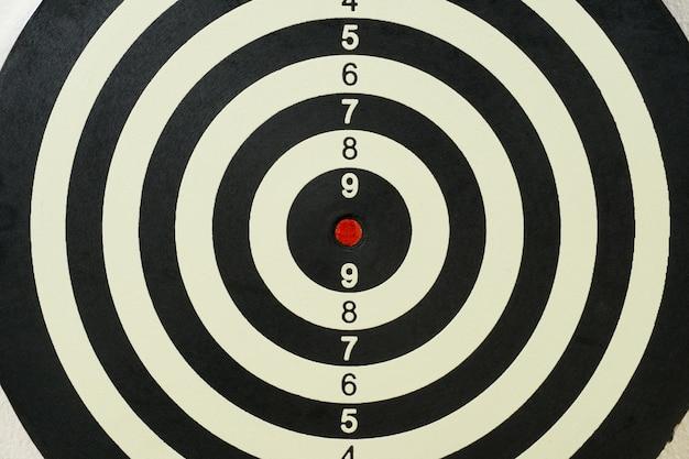 Tablero de dardos con punto rojo en el centro.