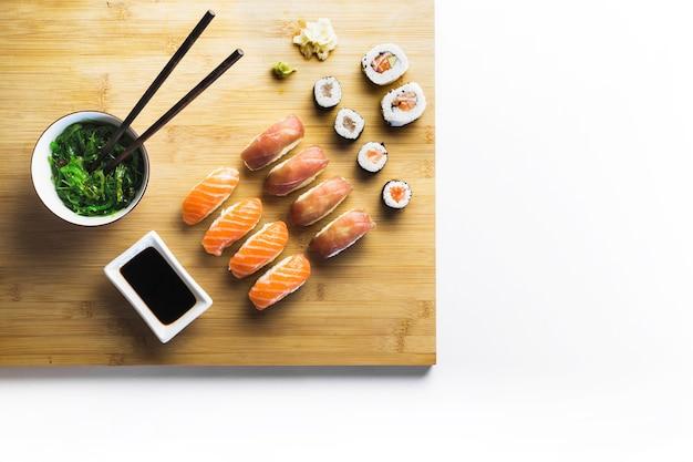 Tablero con ensalada de sushi y algas marinas
