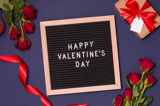 Tablero feliz de la letra del día de tarjetas del día de san valentín con el fondo romántico - rosas rojas, besos y corazones.