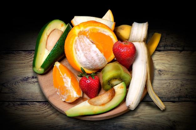 Tablero con fruta, naranja, kiwi, plátano, fresa y aguacate.