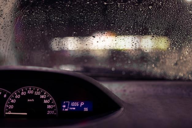 Tablero de instrumentos iluminado y el parabrisas mojado por la lluvia con poca visibilidad, tailandia.