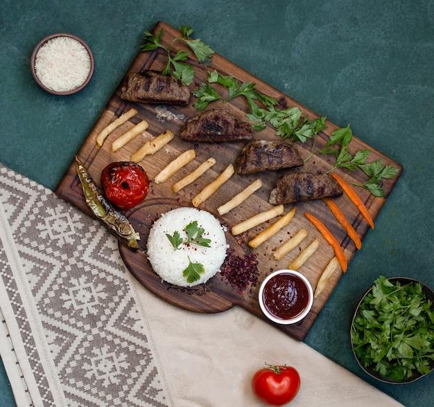 Tablero de kebab de vista superior con alimentos a la parrilla.