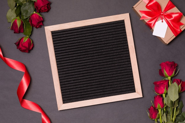 El tablero de la letra imita para arriba para el día de tarjetas del día de san valentín en fondo negro con las rosas rojas y la cinta.