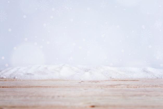 Tablero de madera cerca de montón de nieve y copos de nieve cayendo
