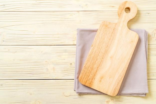 Tablero de madera de corte vacío con fondo de tela de cocina