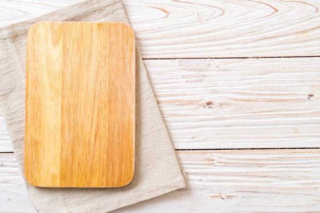 Tablero de madera de corte vacío con paño de cocina sobre fondo de madera, vista superior