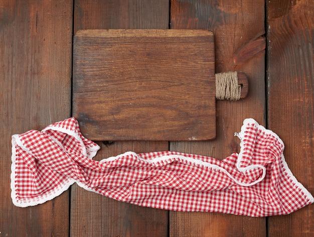Tablero de madera de corte vacío y toalla de cocina roja
