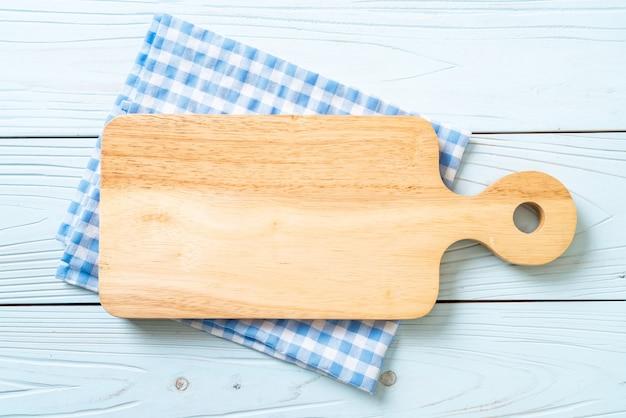 Tablero de madera de corte vacío con trapo de cocina