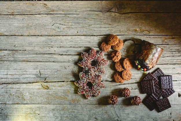 Tablero de madera envejecido retro con las galletas y el caramelo de microprocesador de chocolate en una esquina con el espacio para el texto