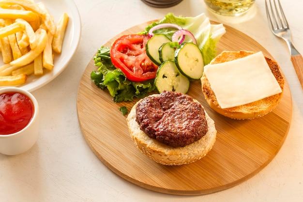 Tablero de madera con hamburguesas y papas fritas