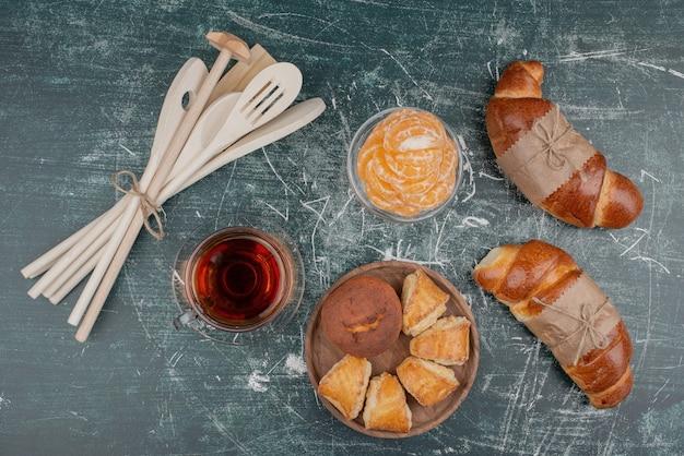 Tablero de madera de panadería con utensilios de cocina sobre superficie de mármol.