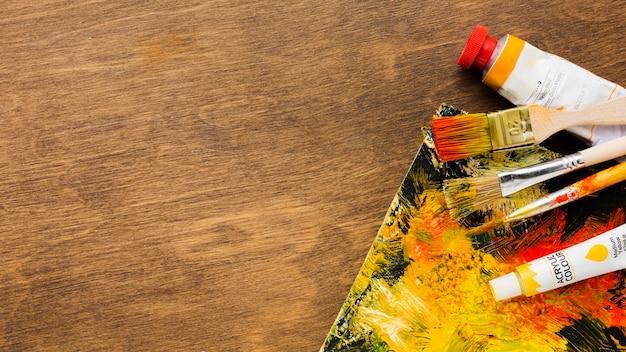 Tablero de madera plano y herramientas de pintura sucias