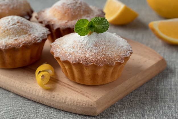 Tablero de madera con sabrosos muffins de limón en la mesa gris