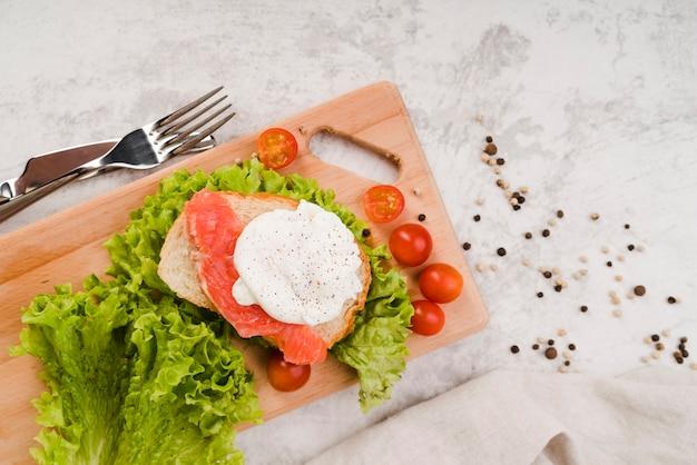 Tablero de madera con sandwich fresco en la mesa