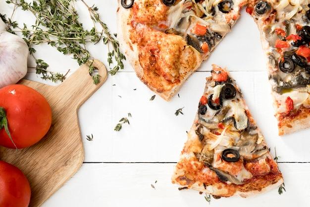 Tablero de madera con verduras y pizza.