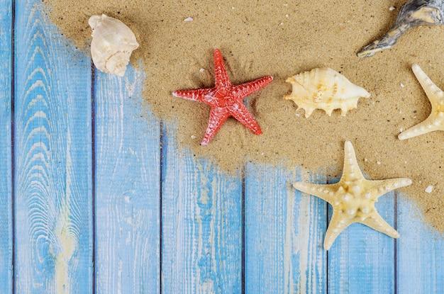 Tablero de madera vieja con conchas de estrellas de mar en la arena de la playa